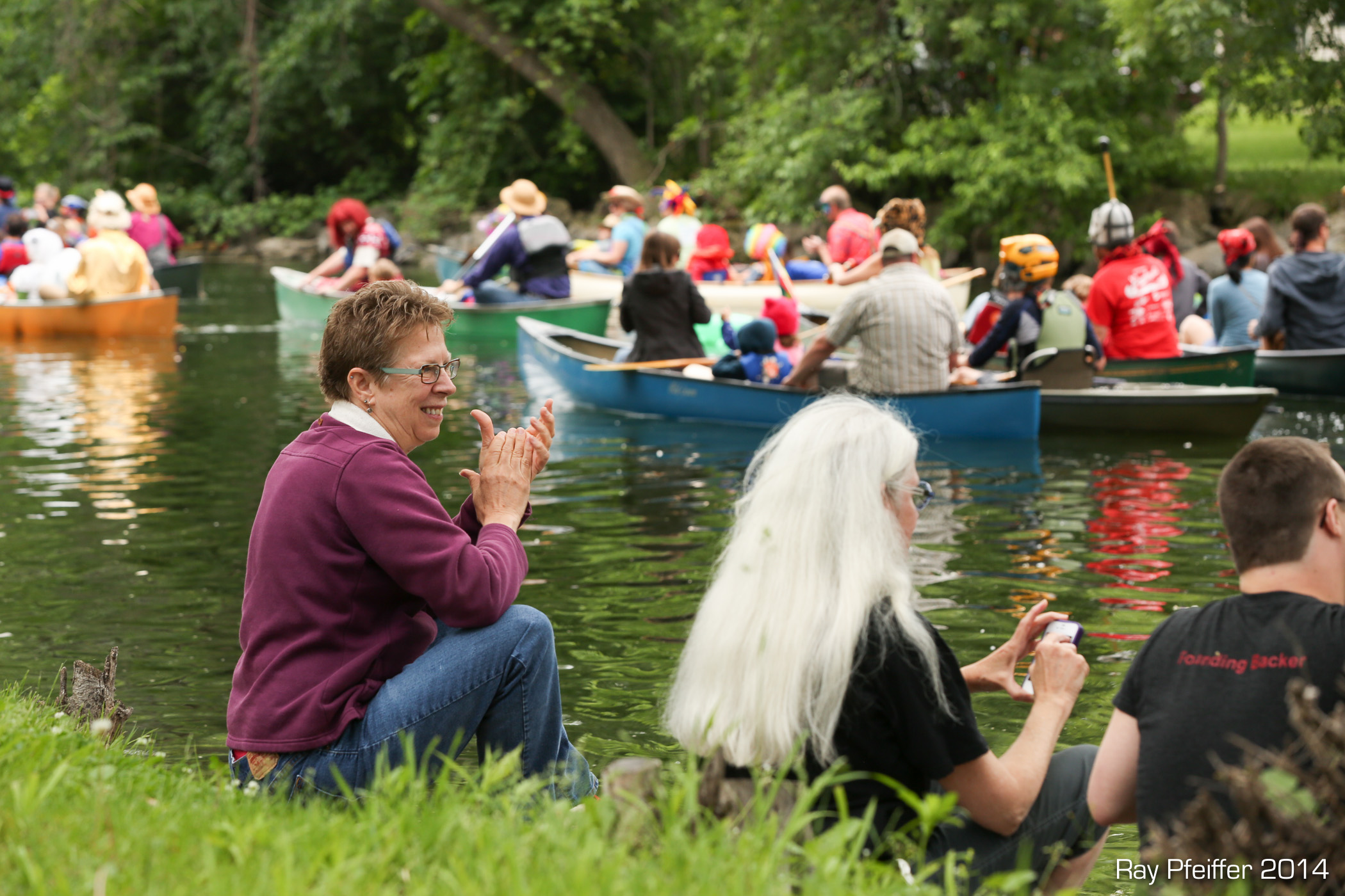 Spectators on the Yahara River banks clapping